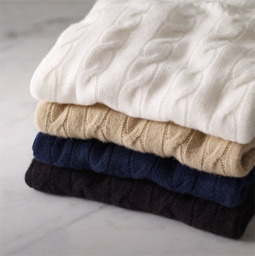 Stack of cable-knit sweaters in white, tan, navy & black