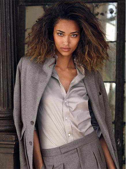 Woman wears grey silk shirt with grey blazer draped over her shoulders