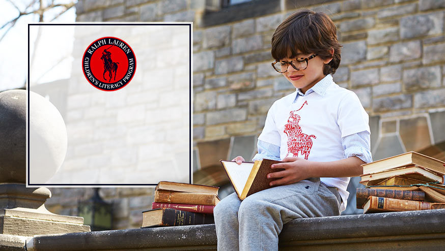 Boy wearing literacy tee reads book