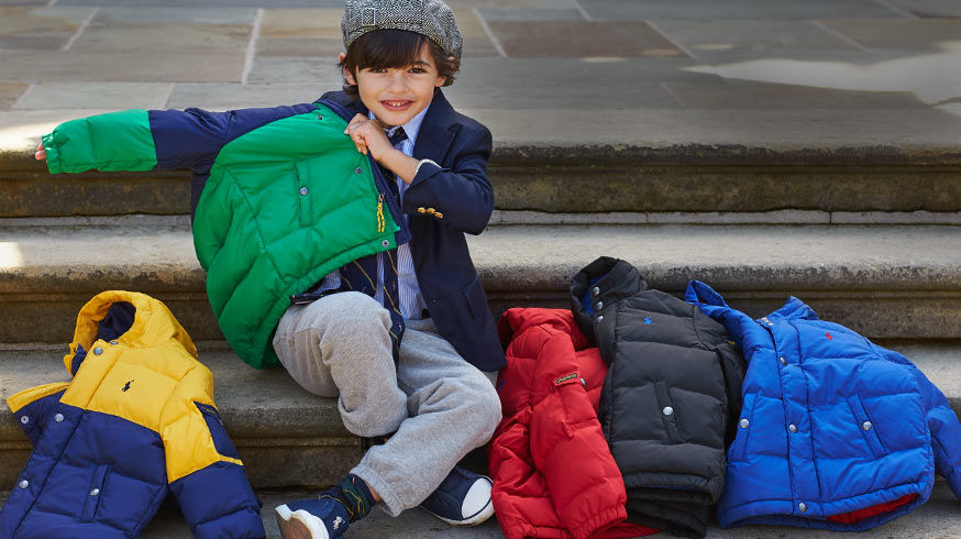 Boy tries on green puffer coat over blazer