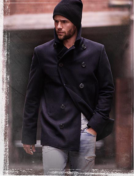 Man models double-breasted coat, denim shirt & knit hat