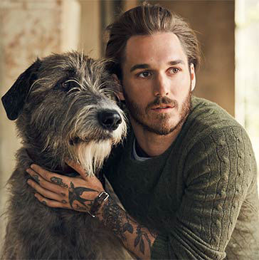 Man in green cable-knit sweater pets shaggy dog