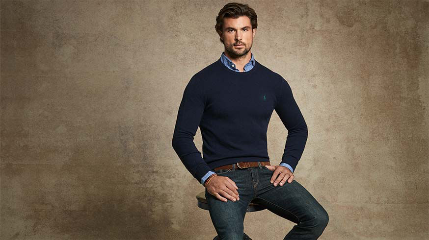 Man layers navy sweater over blue checked shirt