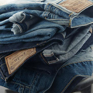 Pile of folded jeans in varying washes