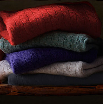 Haphazard stack of folded sweaters in red, green, purple, white & black