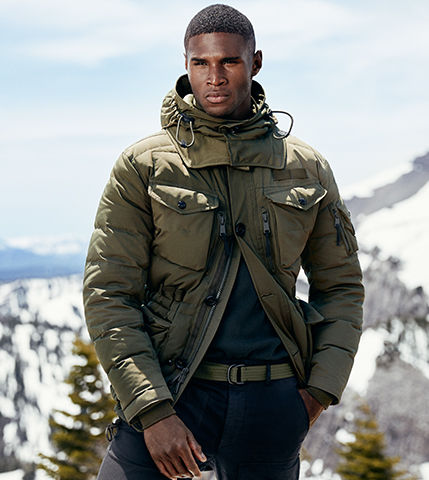 Man in olive-hued utility jacket stands in front of snowy mountains