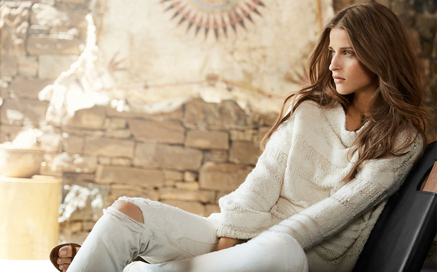 Woman reclines on chair wearing cream sweater & white distressed jeans
