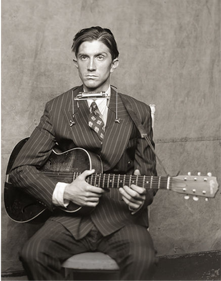 Old-timey photo of man wearing tailored suit & playing guitar
