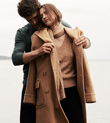 Man draping camel coat over woman's shoulders on beach